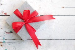 Silver gift box with red ribbon bow on vintage background Stock Photography