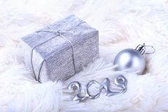 Silver gift box with ribbon bow and Christmas balls on white. Decoration for happy holidays. Silver gift box with ribbon bow and Christmas balls on white royalty free stock image
