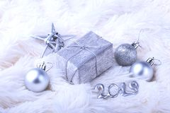 Silver gift box with ribbon bow and Christmas balls on white. Decoration for happy holidays. Silver gift box with ribbon bow and Christmas balls on white stock images