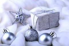 Silver gift box with ribbon bow and Christmas balls on white. Decoration for happy holidays. Silver gift box with ribbon bow and Christmas balls on white royalty free stock photos