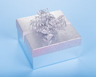 Silver Gift Box. Shiny silver gift box on a blue background Stock Photos