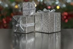 Silver gift boxes Christmas decoration reflected on a table royalty free stock photo