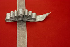 Silver gift ribbon and bow on red background. some Stock Photography