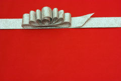 Silver gift ribbon and bow on red background. some Stock Photos
