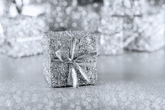 Silver gift with ribbon on a silver background Stock Photos