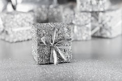 Silver gift with ribbon on a silver background Royalty Free Stock Photo