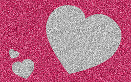 Silver giltter heart on pink glitter Stock Photography