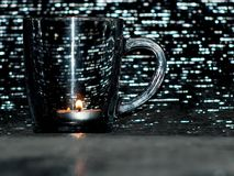 Silver glass or metal cold light. Silver glass or metal cold hot drinks from the background of tea the comfort of home sweet candle substrate on the bottom of Royalty Free Stock Images