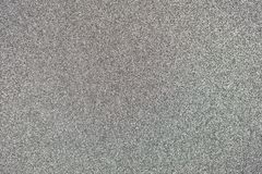 Silver Glitter Background. Dark silver colored sand paper textured background with sparkles and glitters stock images