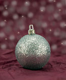 Silver Glitter Bauble. Silver glitter bauble on a red crushed tissue background Royalty Free Stock Photos