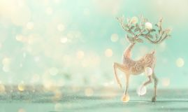 Silver glitter Christmas deer on blue background with lights bokeh, copy space. Greeting card for new year party. Festive holiday. Concept. Banner royalty free stock photo