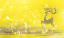 Silver glitter Christmas deer on yellow background with lights bokeh, copy space. Greeting card for new year party. Festive. Holiday concept. Banner stock photos