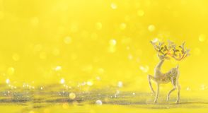 Silver glitter Christmas deer on yellow background with lights bokeh, copy space. Greeting card for new year party. Festive. Holiday concept. Banner stock photography