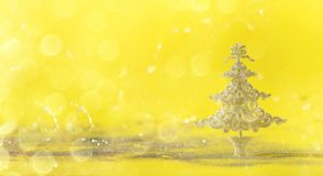 Silver glitter Christmas tree on yellow background with lights bokeh, copy space. Greeting card for new year party. Festive. Holiday concept. Banner royalty free stock photography