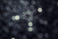 Silver glitter on dark background. Bokeh effect royalty free stock photo