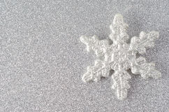 Silver Glitter Snowflake. A sparkly silvery glitter encrusted snowflake on a silver glitter background.  Copy space to left Royalty Free Stock Image