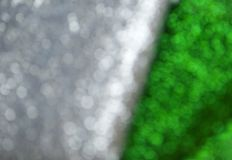 Silver glitter texture. Bokeh effect. Silver and green glittery shimmering background with blinking details stock image