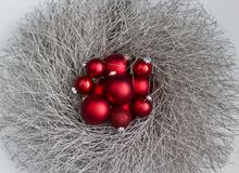 Silver Gltter Wreath with Red Christmas Ornaments. A silver, gltter wreath with red Christmas ornaments against a white background Royalty Free Stock Photography