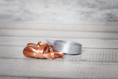 The silver and gold coil of ribbons on a wooden table Royalty Free Stock Photography