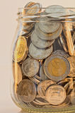 Silver and gold coins in a glass jar Stock Photos