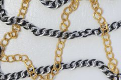 Silver and gold color chains. Chains on white leather background royalty free stock image