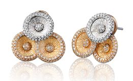 Silver and gold earrings decorated by diamonds Royalty Free Stock Image