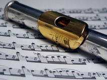 Silver and Gold Flute over sheet music. Silver flute with gold mouthpiece on top of sheet music Royalty Free Stock Image