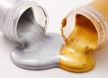 Silver and gold gouache colors. Silver and gold colors, spilled from the jars and mixed Stock Photos
