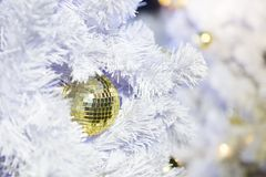 Silver and gold mirror balls on a white Christmas tree. Decorated in Christmas and New Year background royalty free stock images