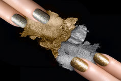 Silver and Gold Nail Polish and Mineral Eye Shadow. Festive nail art. Fingers with trendy gold and silver nail polish and crushed eye shadow with drops of water Stock Photo