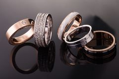 Silver, gold, platinum rings of different styles on the dark background of reflections  Royalty Free Stock Photo