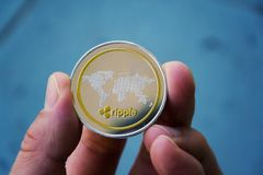 Silver gold ripple coin in hand, cryptocurrency investing concept royalty free stock photos