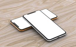 Silver and gold smartphones with blank screen, isolated on wooden background. royalty free stock photos