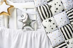 Silver and gold star shaped pillows and patchwork comforter on a white baby cot close up.  Stock Photo