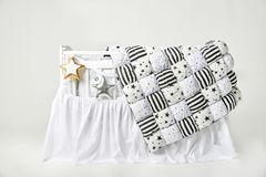 Silver and gold star shaped pillows and patchwork comforter on a white baby cot.  royalty free stock photo