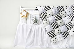 Silver and gold star shaped pillows and patchwork comforter on a white baby cot.  Stock Image