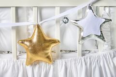 Silver and gold star shaped pillows on a white baby cot Stock Image