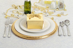 Silver and gold table setting with present Stock Photo