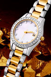 Silver and gold watch. Silver and gold metal watch with crystals or diamonds on chunks of gold background Stock Image