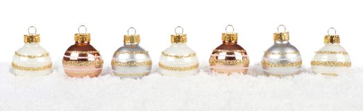 Silver, gold and white Christmas bauble border in snow over white stock photo