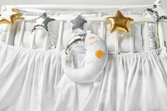 Silver, gold and white star shaped pillows and sleeping moon cushion on a white baby cot.  stock images