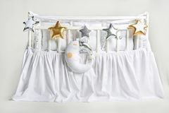 Silver, gold and white star shaped pillows and sleeping moon cushion on a white baby cot. Silver, gold and white star shaped pillows and sleeping moon cushion royalty free stock photo