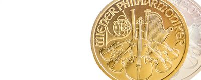 Silver and golden austrian philharmoniker one ounce coins. Closeup of silver and golden austrian philharmoniker one ounce coins on white background placed on royalty free stock photos