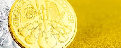 Silver and golden austrian phillharmonikers one ounce coins on golden background royalty free stock images