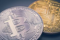 Silver and golden bitcoin physical. Macro shot Stock Images