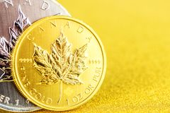Silver and golden canadian maple leaf one ounce coins on golden background. Closeup of silver and golden canadian maple leaf one ounce coins on golden background stock image