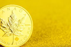 Silver and golden canadian maple leaf one ounce coins on golden background. Closeup of silver and golden canadian maple leaf one ounce coins on golden background royalty free stock photography