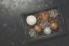 Silver and golden Christmas balls, beads, snowflakes in a wooden vintage tray. Stylish decorations for the Christmas tree. Top. View, flat lay. Place for your stock images