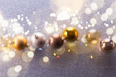Silver and golden christmas bubbles. Row with shining bokeh lights royalty free stock images