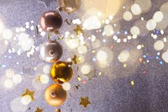 Silver and golden christmas bubbles. With copy space on gray background with shining bokeh lights royalty free stock photo